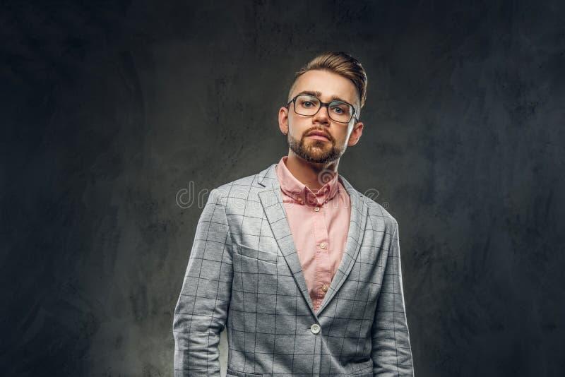Tiro do est?dio do homem novo orgulhoso no blazer quadriculado, nos vidros e na camisa cor-de-rosa imagem de stock royalty free