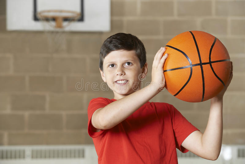Tiro do menino durante o fósforo de basquetebol no Gym da escola fotografia de stock royalty free