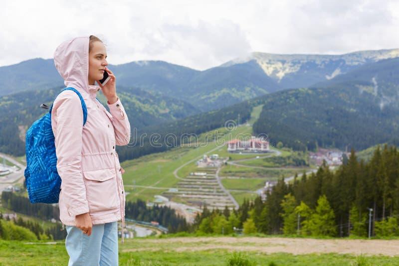 Tiro do perfil do revestimento vestindo da jovem mulher e da trouxa azul que comunicam-se com o telefone celular sobre a montanha imagem de stock royalty free