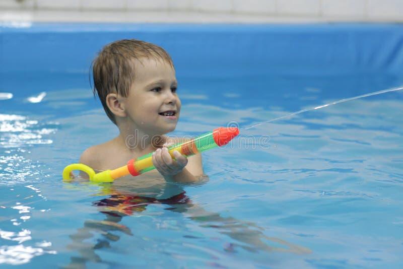 Tiro do rapaz pequeno com a arma de água na piscina fotografia de stock