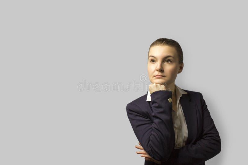 Tiro do retrato mulher de negócio bonita nova com o cabelo curto penteado para trás, vestindo um revestimento com uma cara séria fotografia de stock