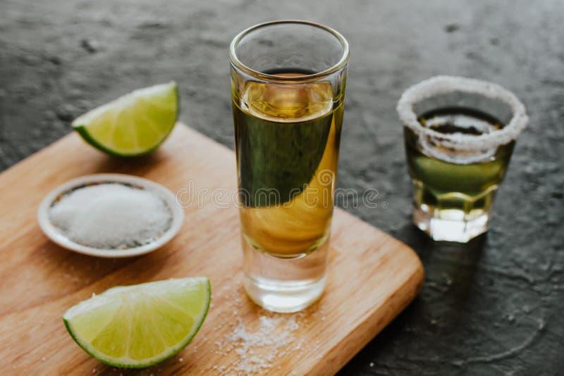 Tiro do Tequila, bebidas fortes alcoólicas mexicanas e partes de cal com sal em México imagem de stock