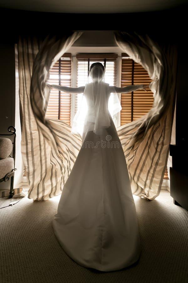 Tiro entonado de las cortinas de abertura jovenes de la novia en la habitación fotografía de archivo