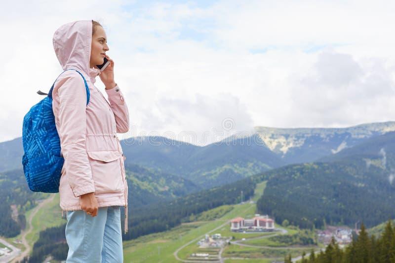 Tiro exterior da fêmea delgada ocupada, estando no monte, falando sobre o telefone, tendo a expressão facial agradável, estando a fotografia de stock