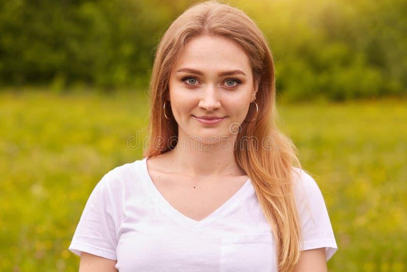 Tiro exterior da menina bonito feliz no prado, jovem senhora de sorriso para apreciar o ar livre, mulher bonita com o cabelo just fotos de stock