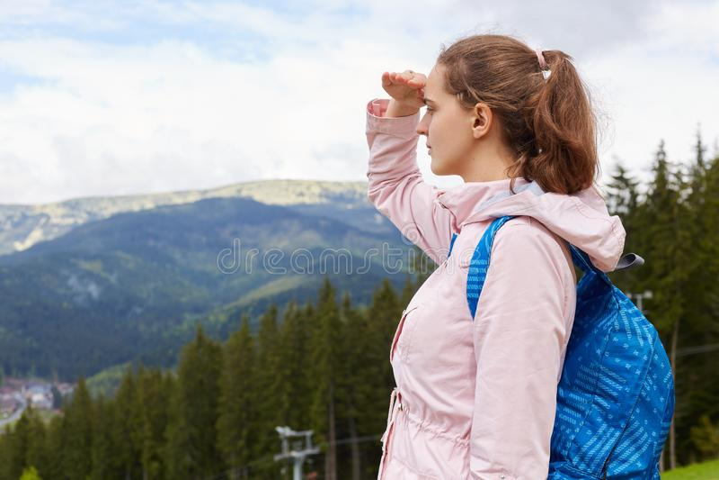 Tiro exterior da posição fêmea atrativa bonito europeia no monte, olhando montanhas, sendo em torno da natureza, cobrindo seus ol fotografia de stock