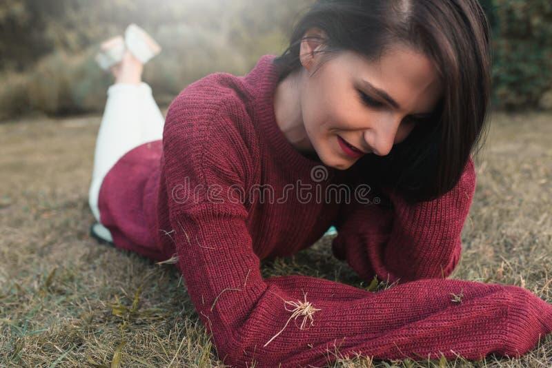 Tiro exterior do retrato de uma mulher caucasiano nova bonita que sorri, pulôver feito malha vestindo, bordos vermelhos, encontra foto de stock royalty free