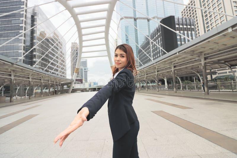 Tiro granangular de la oficina exterior derecha asiática joven atractiva de la mujer de negocios en fondo de la ciudad fotos de archivo