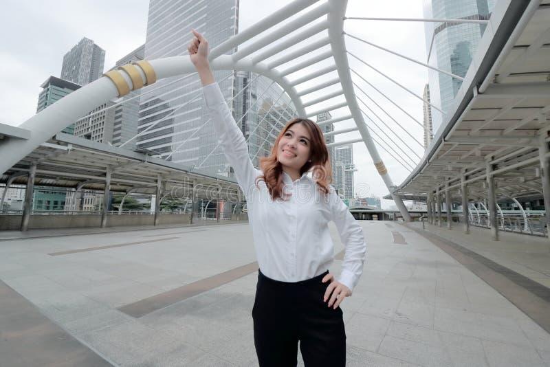 Tiro granangular de la situación asiática joven acertada de la empresaria y de manos rasing en la ciudad constructiva urbana con  fotografía de archivo