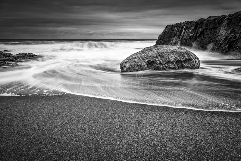 Tiro greyscale bonito das ondas do mar que batem uma rocha a praia fotografia de stock