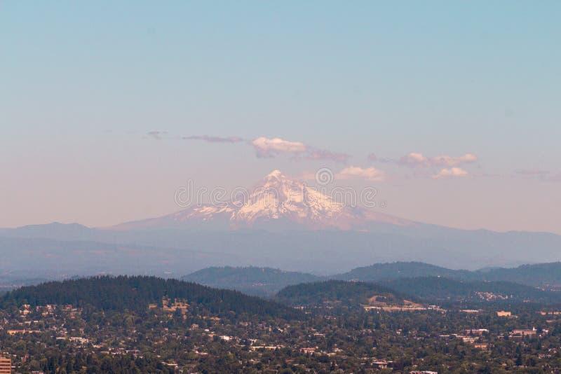 Tiro hermoso ancho de una alta montaña nevada con las colinas y los bosques imagen de archivo libre de regalías