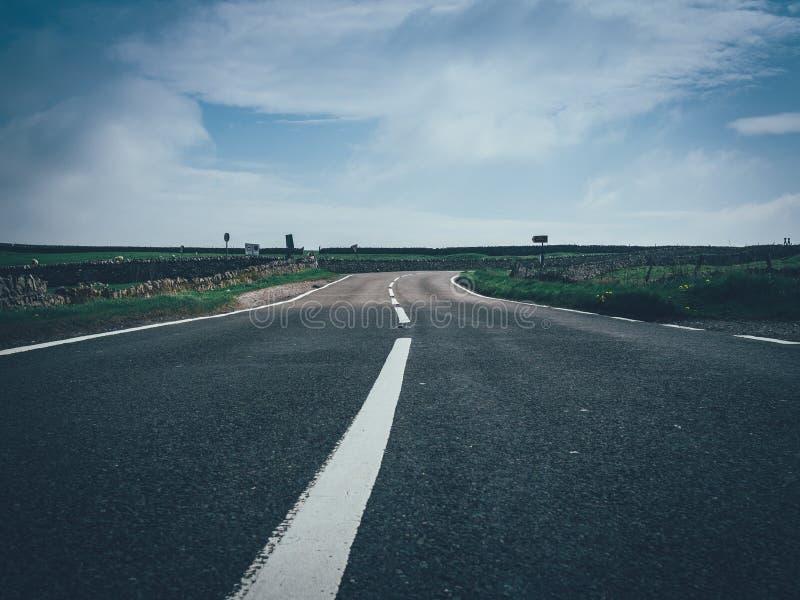 Tiro hermoso de un camino concreto con una línea blanca en el medio de un campo grande imagenes de archivo