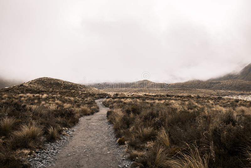 Tiro hermoso de un camino estrecho de la montaña con las nubes y las colinas hermosas en un desierto imagenes de archivo