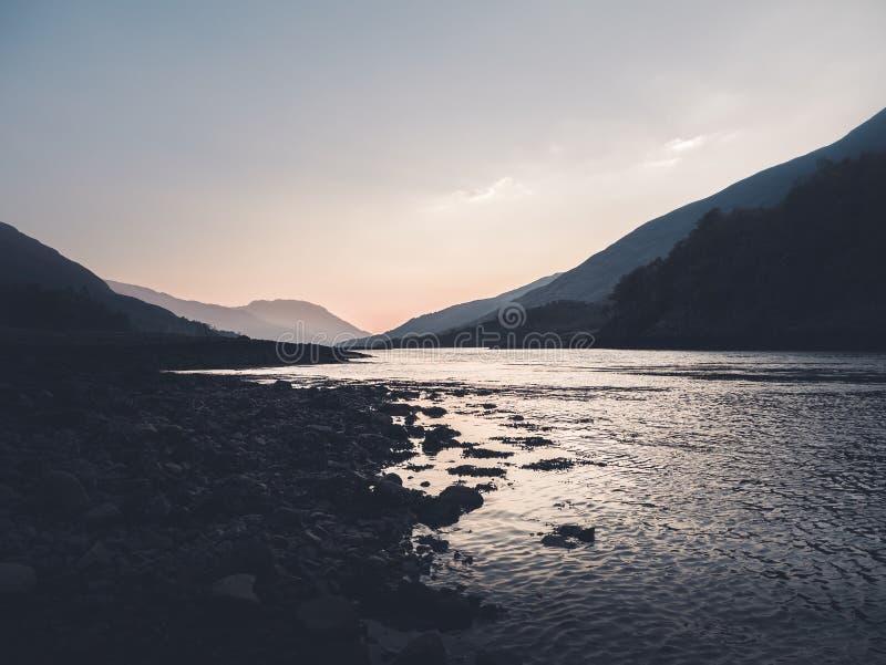 Tiro hermoso de un lago en la salida del sol con las colinas y las montañas en los lados imagen de archivo libre de regalías