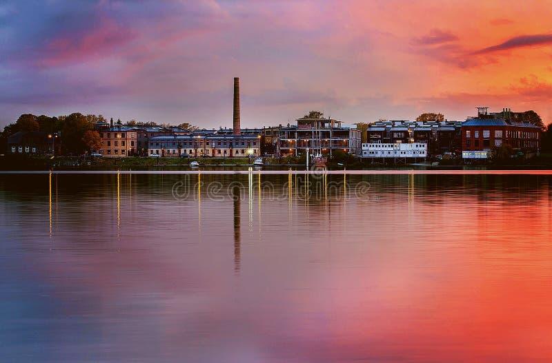 Tiro hermoso de una ciudad en la orilla del lago debajo de un cielo rosado imagenes de archivo