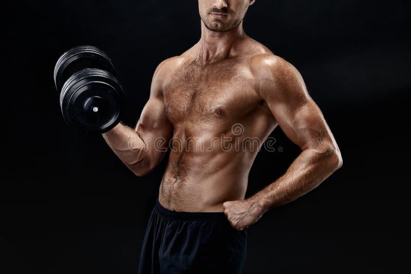 Tiro horizontal cosechado de un culturista joven del ajuste que ejercita con las pesas de gimnasia que presentan en fondo negro imagen de archivo libre de regalías