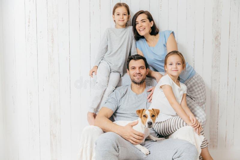 Tiro horizontal da pose amigável da família junto contra b branco imagens de stock