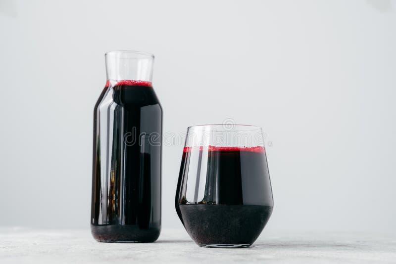 Tiro horizontal de dos envases de cristal llenos de jugo fresco de las remolachas, aislado en el fondo blanco Bebida vitaminada h imagen de archivo libre de regalías