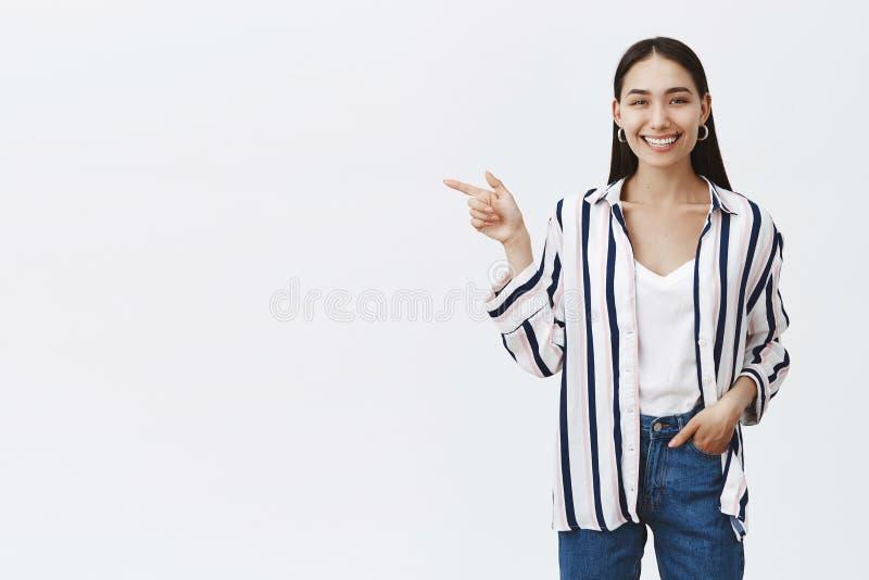 Tiro horizontal de la hembra hermosa feliz optimista en blusa rayada y vaqueros, llevando a cabo la mano en bolsillo y señalar imagen de archivo