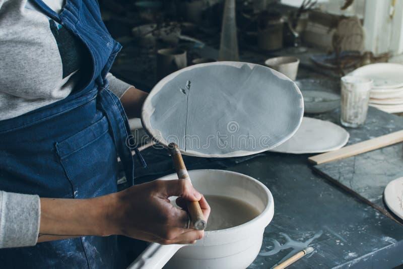 Tiro horizontal de la mujer del artista que sostiene un plato de la arcilla imagen de archivo