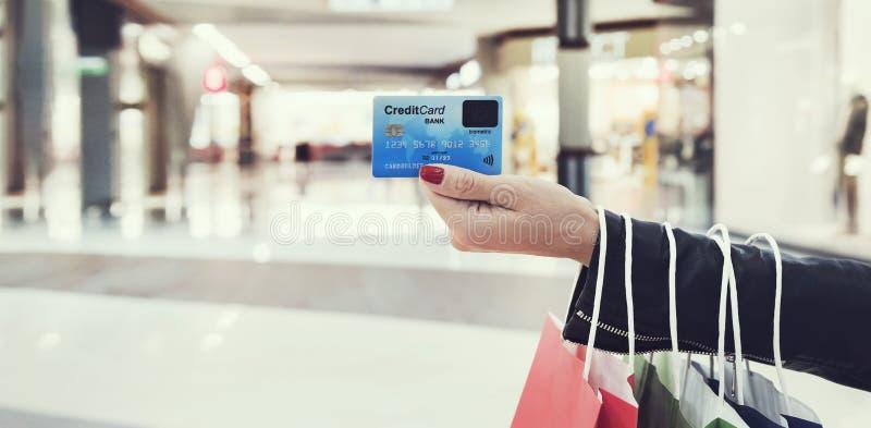 Tiro horizontal de la tenencia femenina de la mano de la cosecha de cara mayor de tarjeta de crédito legible en el fondo de la al fotos de archivo