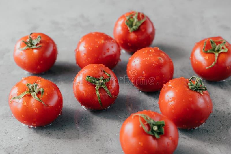 Tiro horizontal de las verduras frescas maduras cosechadas en jardín Tomates rojos con descensos del agua en fondo gris Tiro macr foto de archivo