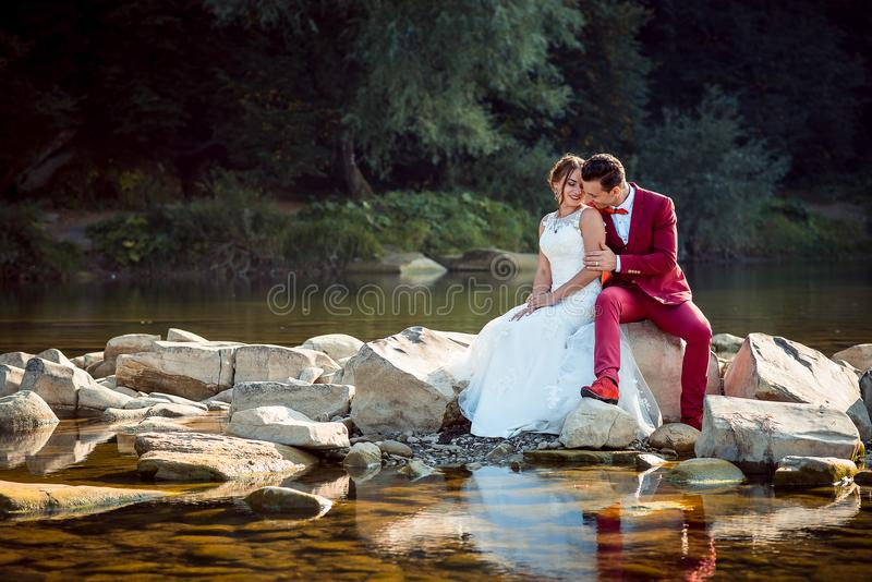 Tiro horizontal de los pares encantadores alegres del recién casado que ríen y que se sientan en los snotes cerca del río hermoso foto de archivo libre de regalías