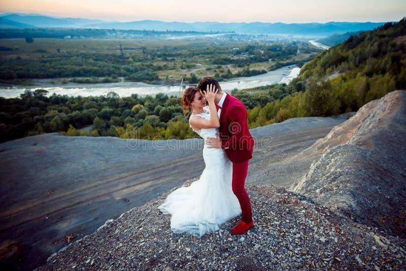 Tiro horizontal de los recienes casados de moda atractivos que abrazan el dge de la roca La novia encantadora del pelo del jengib imagen de archivo libre de regalías