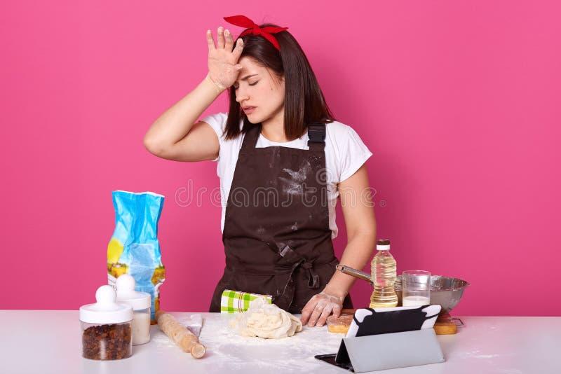 Tiro horizontal del ama de casa agotada cansada que está en la cocina, cerrándose los ojos, tocando su frente con la mano, t blan foto de archivo
