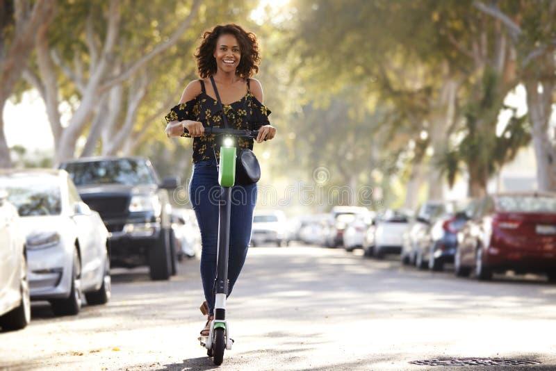 Tiro integral de la mujer afroamericana milenaria que monta una vespa eléctrica en la calle imagen de archivo libre de regalías