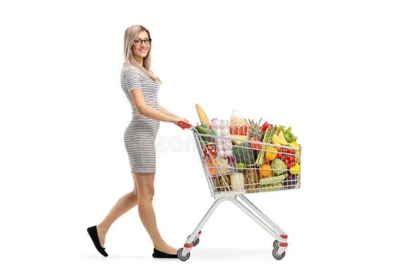 Tiro integral de una mujer atractiva joven que empuja un carro de la compra con los productos alimenticios y que sonríe en la c imagen de archivo libre de regalías