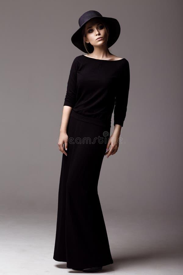 Tiro integral de una mujer en vestido y sombrero negros largos fotos de archivo libres de regalías