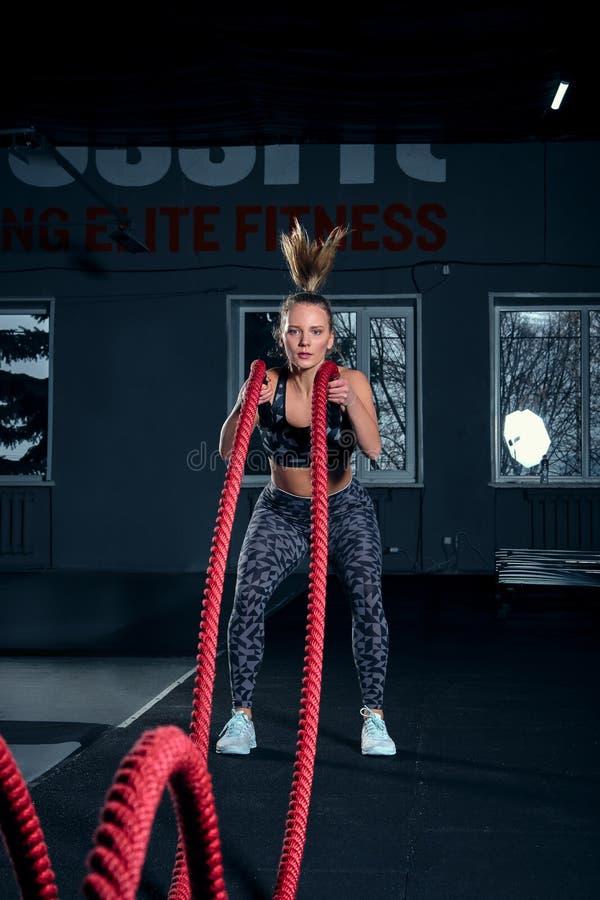 Tiro integral vertical de una mujer atlética de la aptitud que hace ejercicio de formación funcional con las cuerdas de la batall foto de archivo libre de regalías
