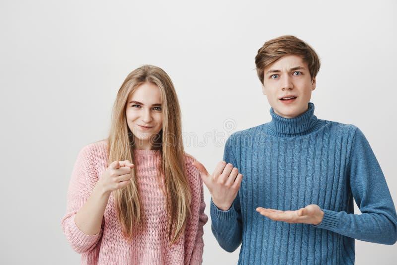 Tiro interior de los suéteres coloridos que llevan femeninos masculinos y que fruncen el ceño chocados que miran la cámara Muchac imagenes de archivo