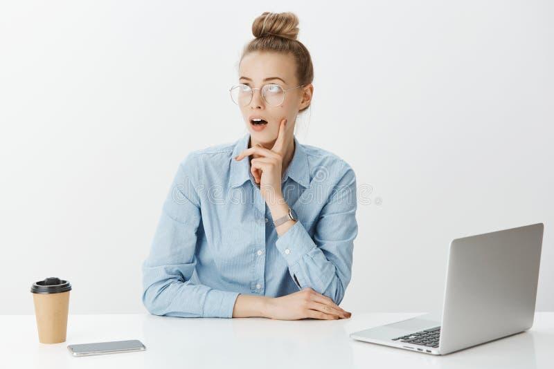 Tiro interior del compañero de trabajo femenino creativo soñador con el pelo rubio en vidrios, teniendo idea o plan mientras que  imagenes de archivo