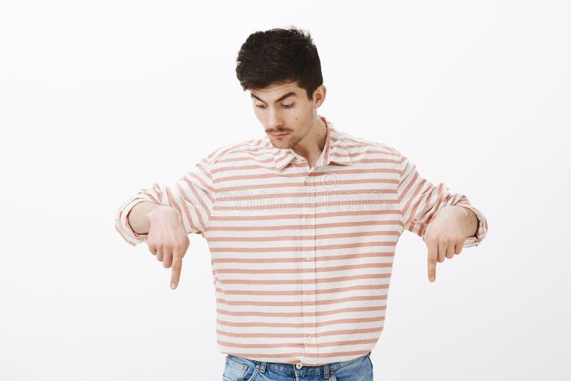 Tiro interior del compañero de trabajo masculino caucásico curioso sorprendente en camisa rayada, señalando abajo con los dedos í imagenes de archivo