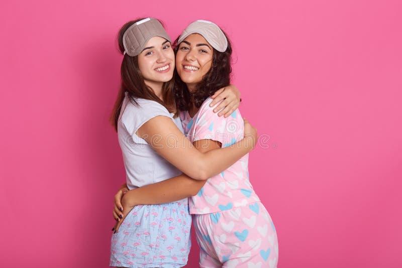 Tiro interior del estudio de los amigos hermosos sinceros que presentan sobre fondo rosado, abrazándose, sonriendo, teniendo agra fotos de archivo libres de regalías