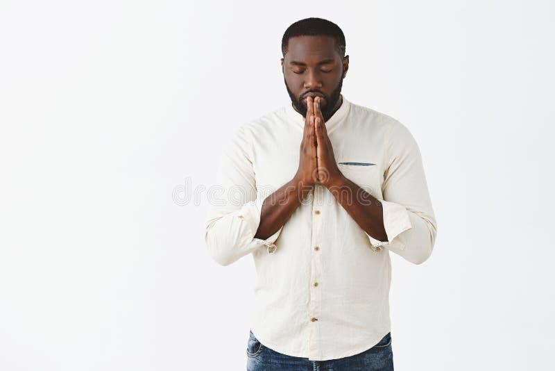 Tiro interior del hombre afroamericano muy serio enfocado y determinado en la camisa blanca, ojos de cierre, llevando a cabo las  fotos de archivo libres de regalías