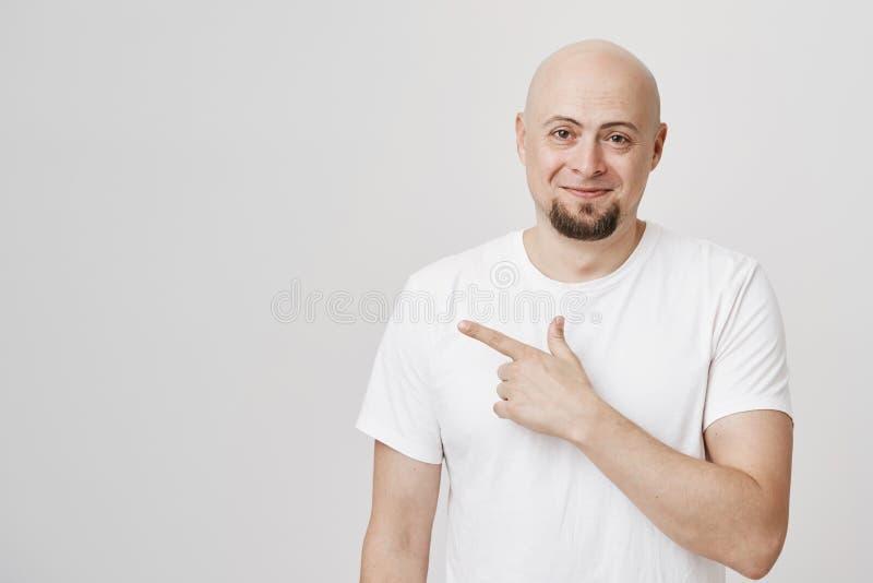 Tiro interior del hombre europeo calvo hermoso con la barba, la camiseta blanca que lleva y señalar a la izquierda y la sonrisa a foto de archivo libre de regalías