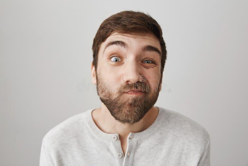 Tiro interior del individuo barbudo divertido atractivo que bizquea y que hace caras en la cámara, estando en buen humor mientras foto de archivo