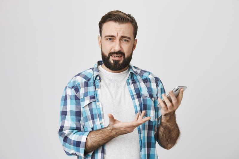 Tiro interior del individuo caucásico con la barba y del bigote en camisa comprobada, llevando a cabo el teléfono y gesticular, e imagen de archivo