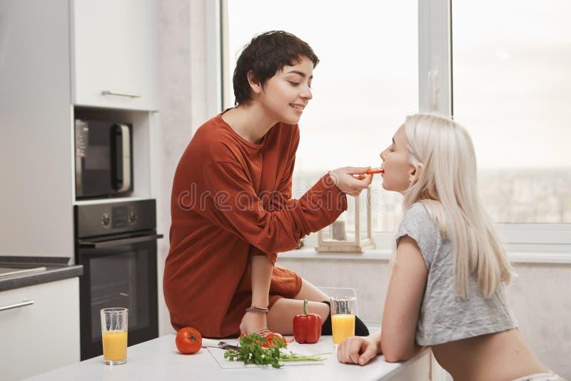 Tiro interior dulce y lindo de la mujer camisa-cabelluda caliente que alimenta a su novia mientras que se sienta en la tabla y la fotografía de archivo libre de regalías