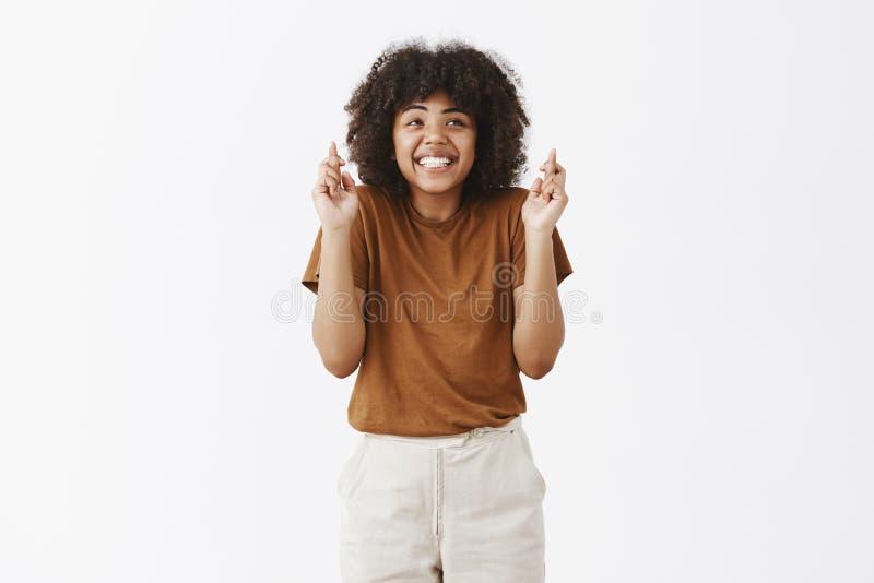 Tiro interno da fêmea de pele escura otimista sonhadora encantador no t-shirt marrom que shrugging da impaciência que sorri ampla foto de stock royalty free