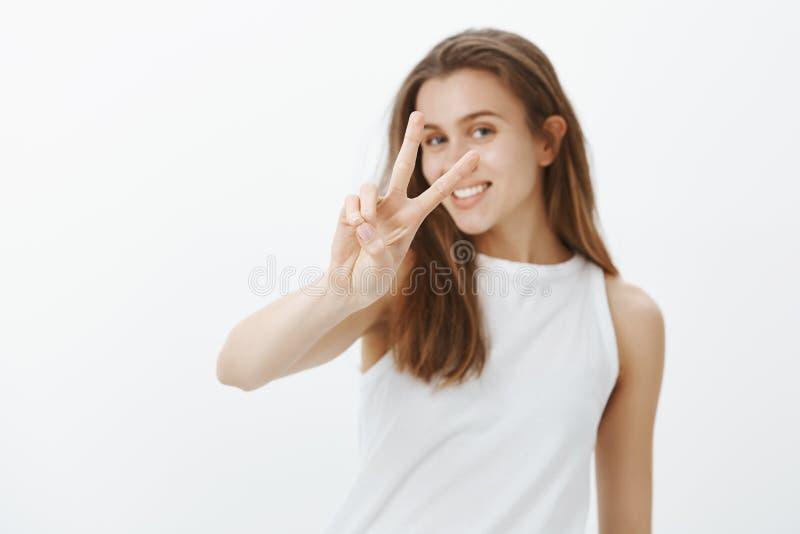 Tiro interno da mulher europeia bonita feliz com cabelo louro, puxando a mão para a câmera e mostrando a vitória ou fotografia de stock
