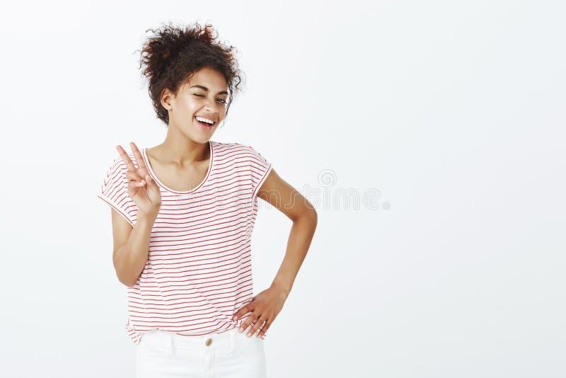 Tiro interno da mulher feliz e que parte segura com pele bronzeada, guardando a mão no quadril, mostrando a vitória ou a paz fotografia de stock royalty free
