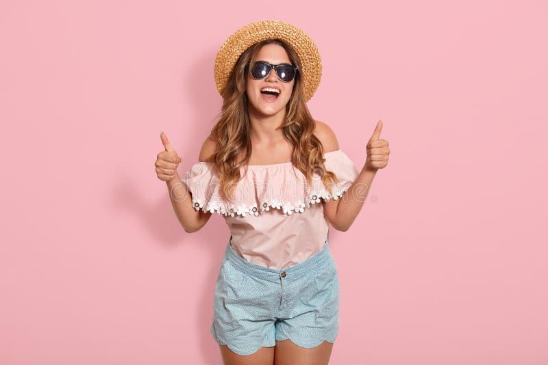 Tiro interno da mulher feliz nova atrativa com cabelo longo, roupa à moda vestindo, levantando com expressão inspirada da cara at foto de stock