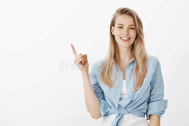 Tiro interno da mulher loura à moda criativa com sorriso largo, aumentando o indicador ao apontar no canto esquerdo superior imagens de stock royalty free