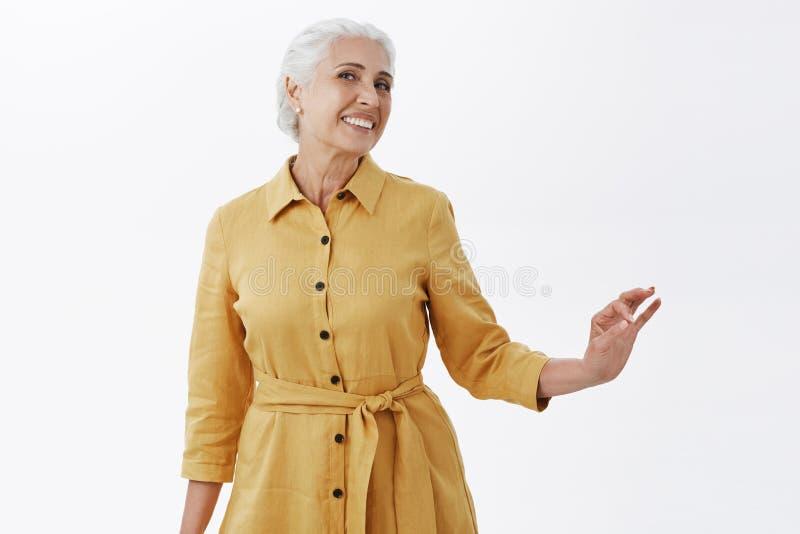 Tiro interno da mulher superior à moda e consideravelmente elegante feliz no revestimento amarelo na moda que levanta com o elleg imagem de stock royalty free