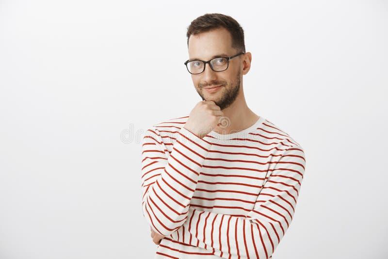 Tiro interno do barman alegre adulto bonito em vidros pretos, em barba tocante e no sorriso curiosamente, verificando para fora a imagens de stock