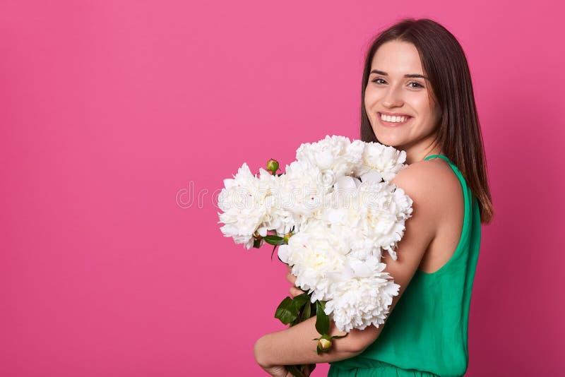Tiro interno do estúdio do grupo da terra arrendada do modelo de flores magnético encantador, tendo o sorriso sincero, vestido ve fotos de stock
